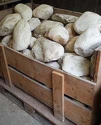 Holzkiste mit Marmorsteinen